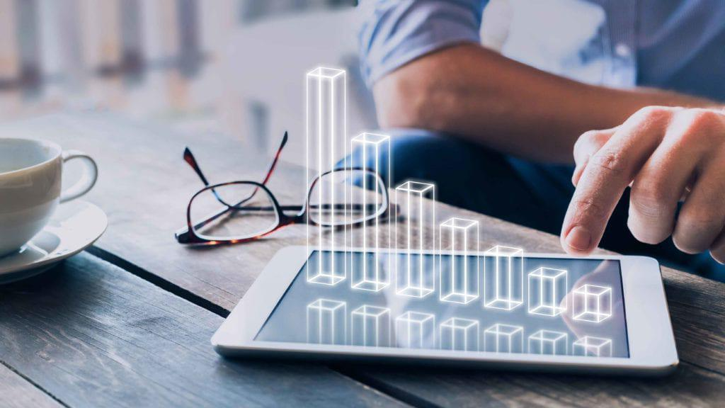 商人分析在数字平板电脑屏幕上方浮动的3D AR图表, 显示企业利润的成功增长